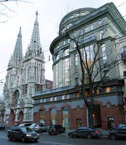 Костел Св. Миколая (ліворуч), сучасний псевдомодерн (праворуч)